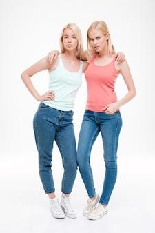 Duas jovens mulheres sérias vestindo camisetas e jeans posando