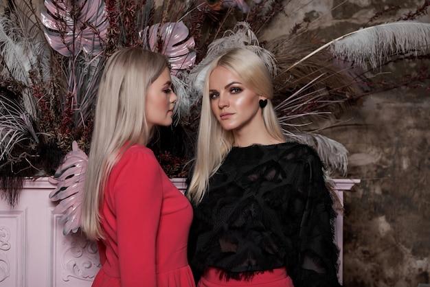 Duas jovens mulheres sexy, com longos cabelos loiros elegantes e maquiagem glamourosa elegante e vestidos vermelhos perto do piano