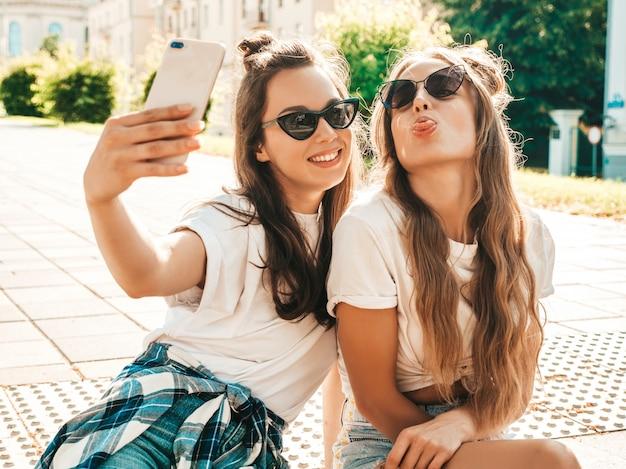 Duas jovens mulheres sorridentes e hipster com roupas de verão