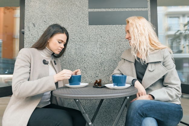 Duas jovens mulheres sorridentes em um café ao ar livre