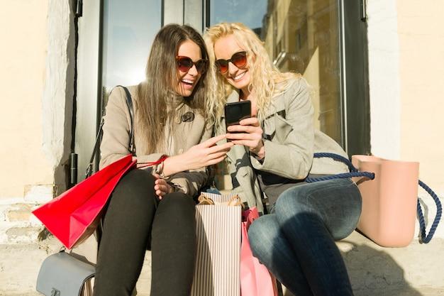 Duas jovens mulheres sorridentes em uma cidade com sacolas de compras