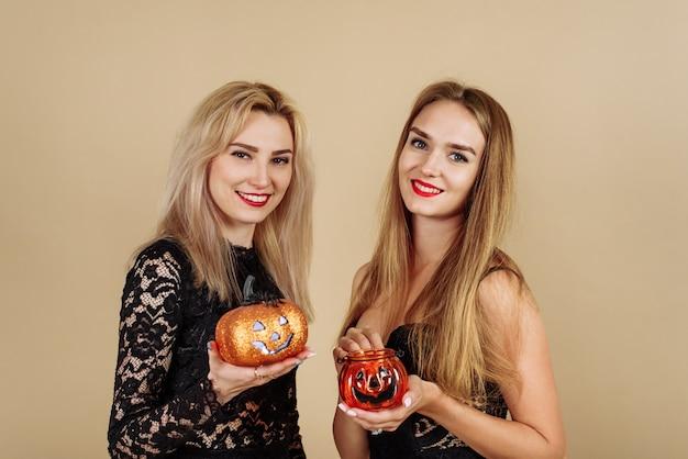 Duas jovens mulheres sorridentes segurando abóboras de halloween em um fundo bege