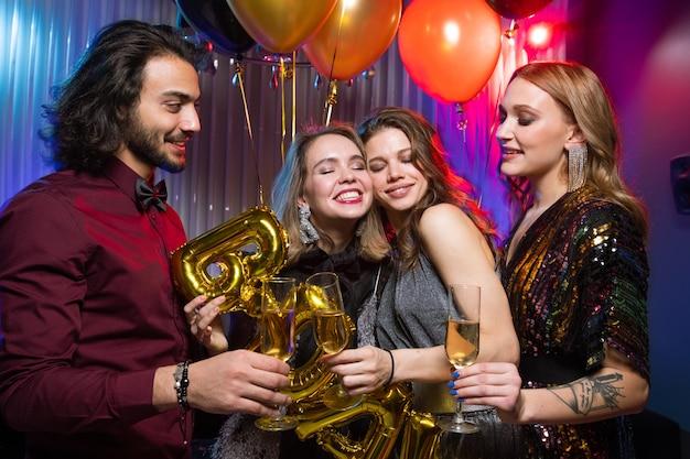 Duas jovens mulheres sorridentes tilintando taças de champanhe com um homem elegante enquanto aproveitam a festa de aniversário na boate