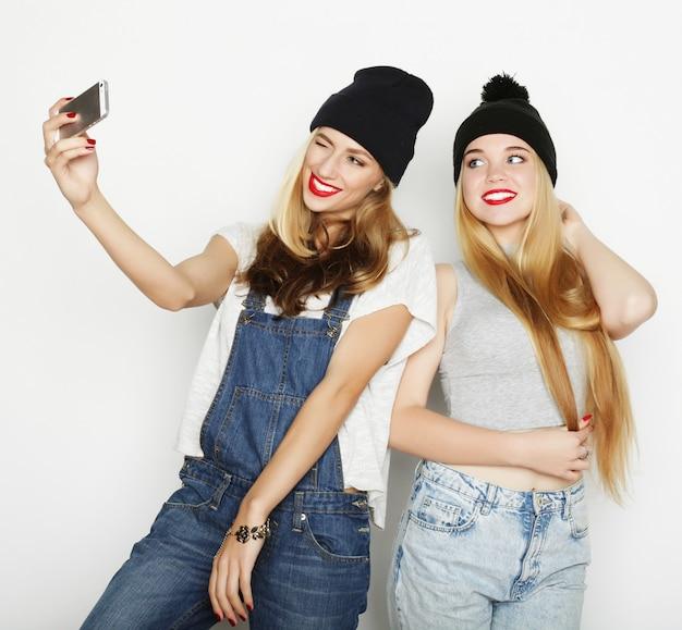 Duas jovens mulheres tomando selfie com telefone móvel