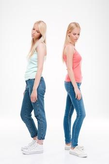 Duas jovens mulheres tristes vestidas com camisetas e jeans posando. isolado sobre parede branca