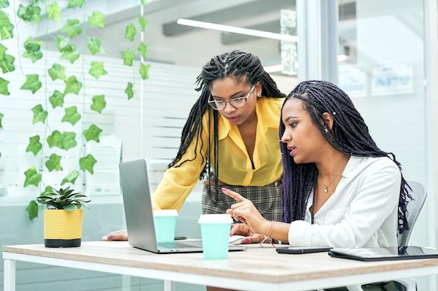 Duas jovens negras revisando dados analíticos em vários dispositivos eletrônicos