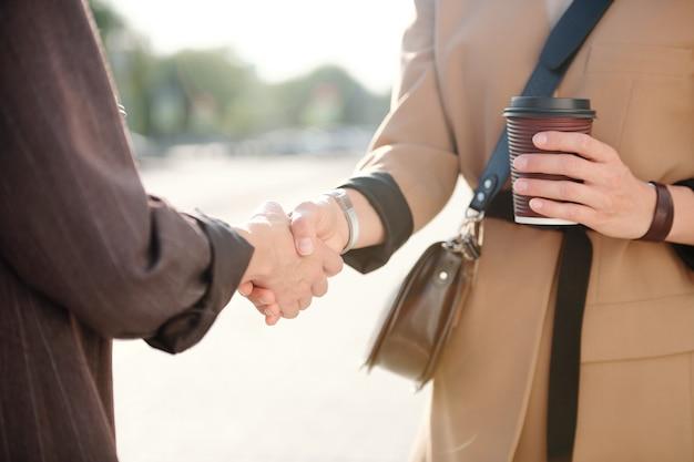 Duas jovens parceiras de negócios bem-sucedidas apertando as mãos depois de negociar e fazer acordo em reunião em ambiente urbano