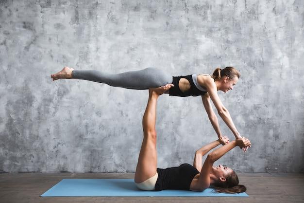 Duas jovens praticando poses de ioga e asanas