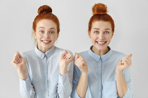Duas jovens ruivas atraentes e felizes com nós de cabelo e camisetas azuis claras