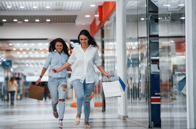 Duas jovens se divertem e correm. ter um dia de compras juntos no supermercado.