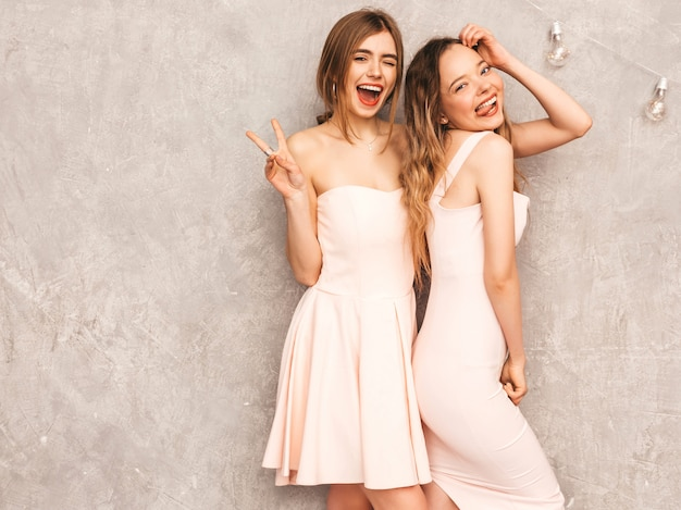 Duas jovens sorridentes lindas meninas na moda verão luz rosa vestidos. mulheres sexy despreocupadas posando. modelos positivos se divertindo e mostrando paz e língua