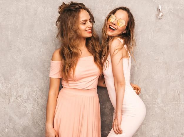 Duas jovens sorridentes lindas meninas na moda verão luz rosa vestidos. mulheres sexy despreocupadas posando. modelos positivos se divertindo em óculos de sol redondos