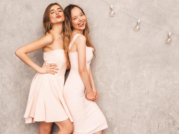 Duas jovens sorridentes lindas meninas na moda verão luz rosa vestidos. mulheres sexy despreocupadas posando. modelos positivos se divertindo