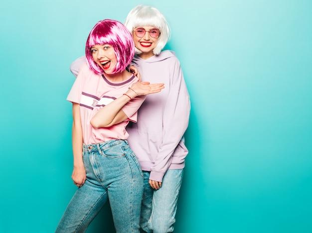 Duas jovens sorridentes sexy hipster garotas em perucas e lábios vermelhos. belas mulheres na moda em roupas de verão. modelos despreocupados posando perto de parede azul no estúdio enlouquecendo e abraçando em óculos de sol