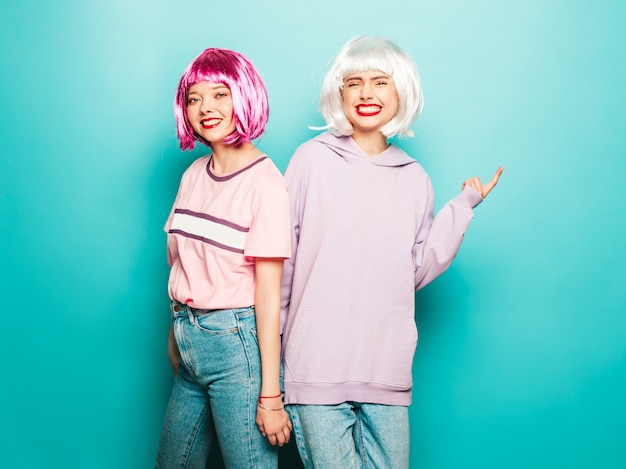 Duas jovens sorridentes sexy hipster garotas em perucas e lábios vermelhos. belas mulheres na moda em roupas de verão. modelos despreocupados posando perto de parede azul no estúdio enlouquecendo e abraçando