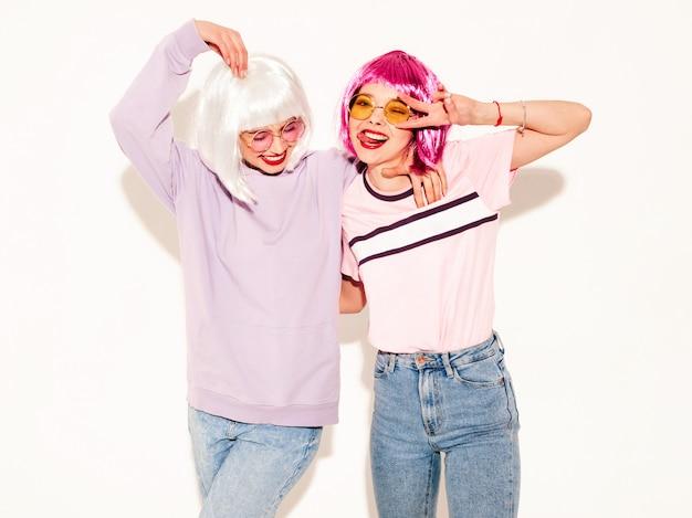 Duas jovens sorridentes sexy hipster garotas em perucas e lábios vermelhos. belas mulheres na moda em roupas de verão. modelos despreocupados posando perto de parede branca no estúdio mostra sinal de paz