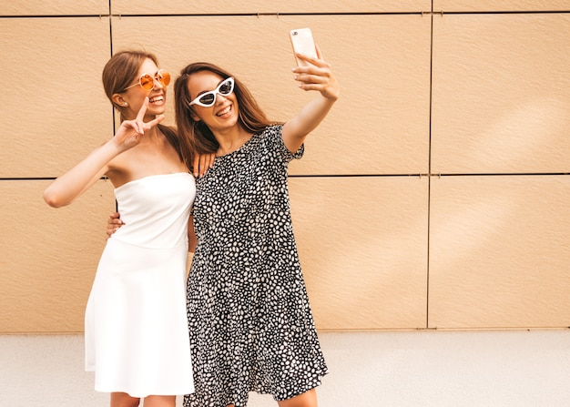 Duas jovens sorrindo hipster mulheres em roupas de verão.