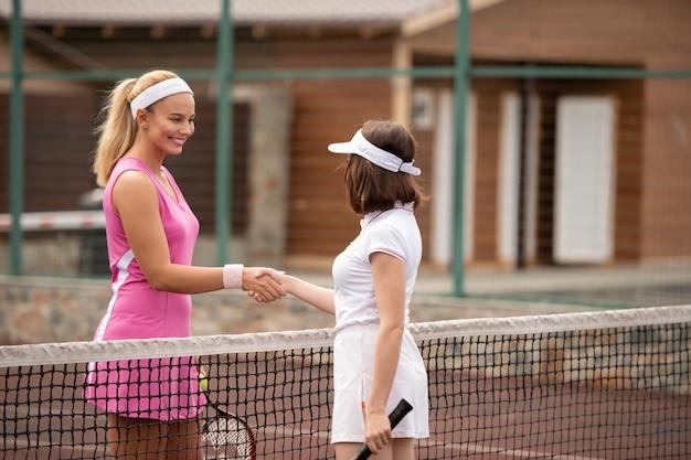 Duas jovens tenistas sacudindo as mãos sobre a rede antes do jogo no estádio