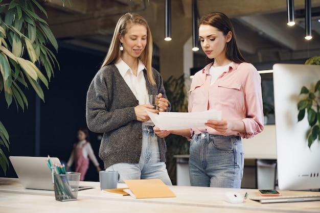 Duas jovens trabalhando juntas no escritório