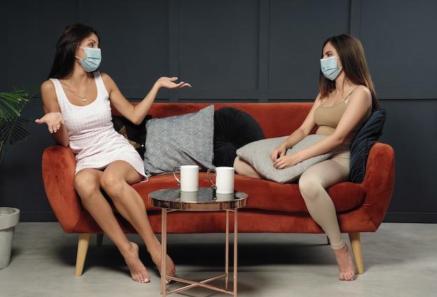 Duas jovens usando máscara enquanto estão sentadas no sofá em casa