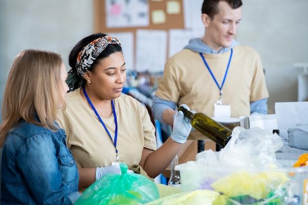 Duas jovens voluntárias olhando para uma garrafa de vinho limpa e vazia contra um homem