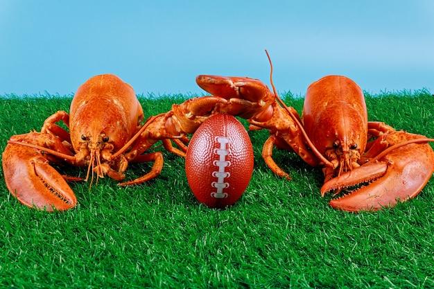 Duas lagostas vermelhas como competidor de um jogo com uma bola de futebol.