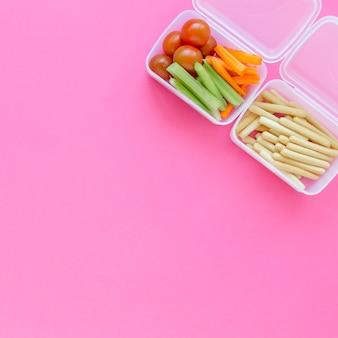 Duas lancheiras com comida escolar