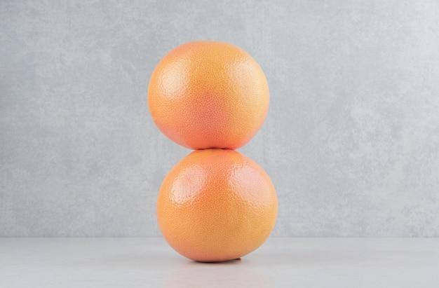 Duas laranjas frescas na mesa de pedra.