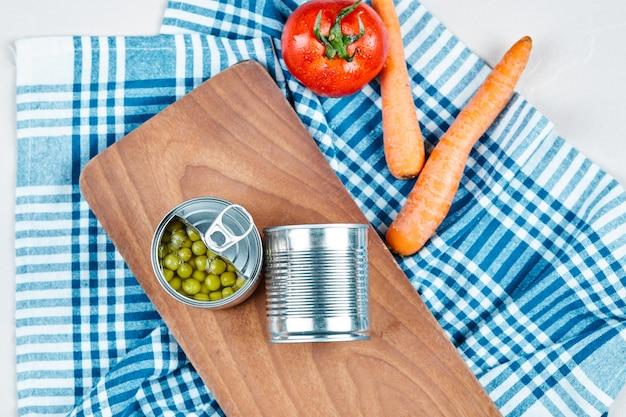 Duas latas de ervilhas cozidas, legumes e toalha de mesa.