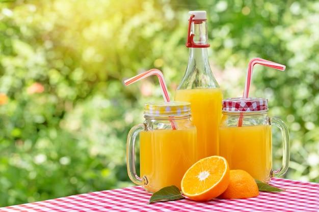 Duas latas e garrafa com suco de laranja na toalha de mesa quadriculada vermelha