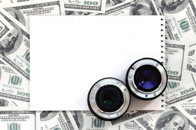 Duas lentes fotográficas e caderno branco encontram-se no fundo