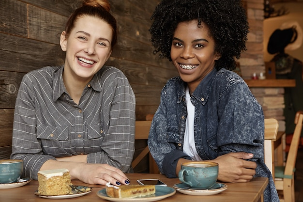 Duas lésbicas africanas e caucasianas felizes desfrutando de um bom tempo juntas durante o almoço em um café aconchegante