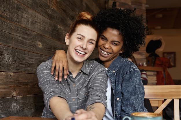 Duas lésbicas alegres rindo e se abraçando enquanto tomam café, sentadas à mesa em um café aconchegante