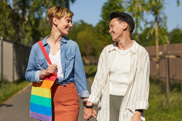 Duas lésbicas felizes sorrindo e conversando enquanto caminhavam pela rua