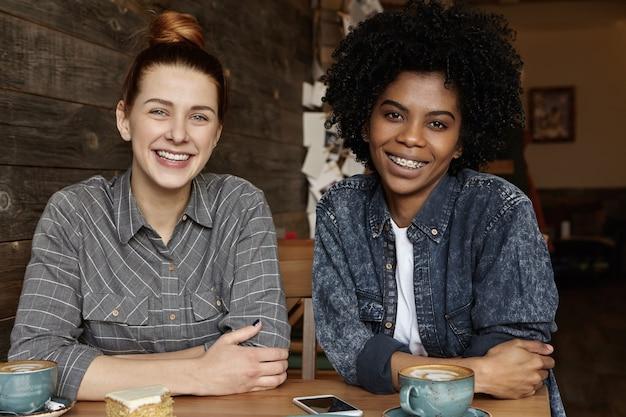 Duas lésbicas felizes tomando café, sentadas à mesa em um restaurante aconchegante