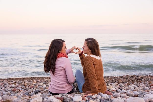 Duas lésbicas sentadas na praia, assistindo e curtindo um belo pôr do sol juntos