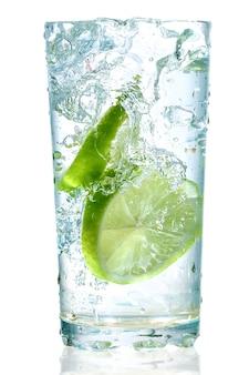 Duas limas caíram em um copo com água isolada no branco
