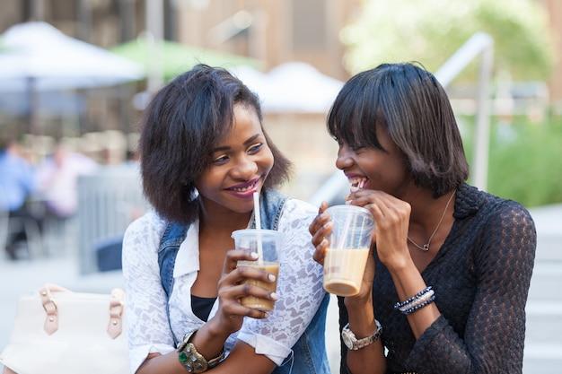Duas linda mulher negra, desfrutando de bebidas refrescantes em nova york