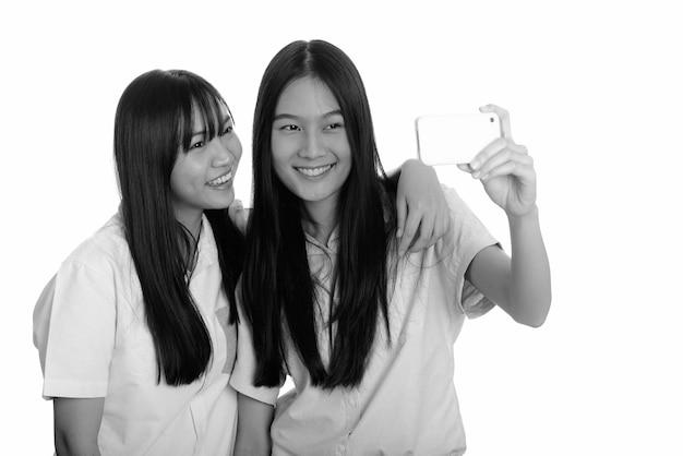 Duas lindas adolescentes asiáticas juntas isoladas contra uma parede branca em preto e branco