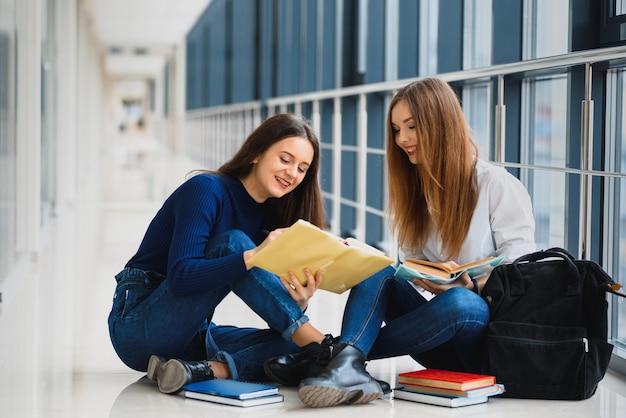 Duas lindas alunas com livros sentadas no chão no corredor da universidade