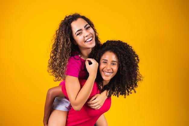 Duas lindas amigas afro se abraçaram, conceito de melhores amigas e irmãs.