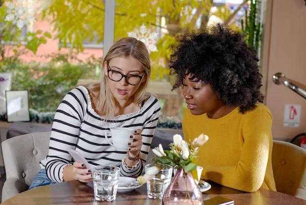 Duas lindas amigas desfrutando de um café juntos em uma cafeteria.