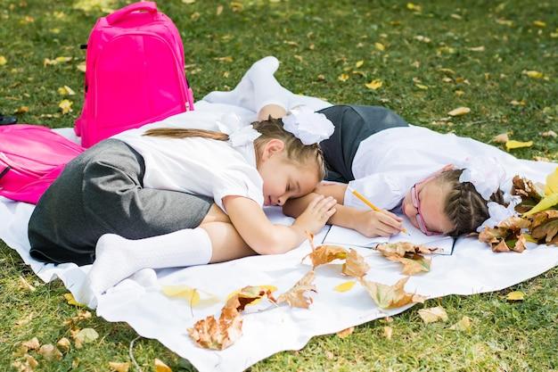 Duas lindas colegiais estavam cansadas de fazer seus deveres de casa e adormeceram em um cobertor em um parque ensolarado de outono. educação ao ar livre. conceito de volta às aulas