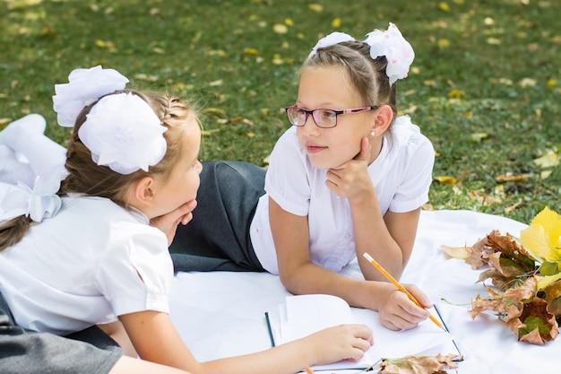 Duas lindas colegiais olham uma para a outra, sorriem e refletem sobre o dever de casa em um cobertor em um parque ensolarado de outono. educação ao ar livre. conceito de volta às aulas