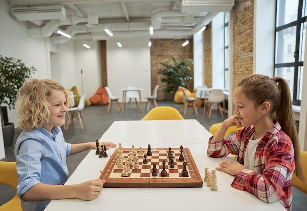 Duas lindas crianças caucasianas, menino e menina, sorrindo enquanto jogavam xadrez, sentados juntos no