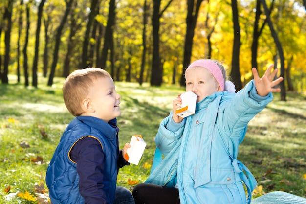 Duas lindas crianças sentadas no chão em uma floresta colorida de outono tomando uma bebida refrescante