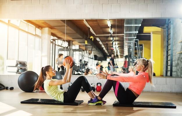 Duas lindas damas em uma academia, sentadas uma contra a outra fazendo flexões passando a bola uma para a outra.