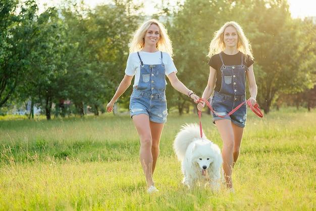 Duas lindas e charmosas gêmeas loiras em macacão jeans estão correndo com um cachorro samoiedo branco fofo no parque.