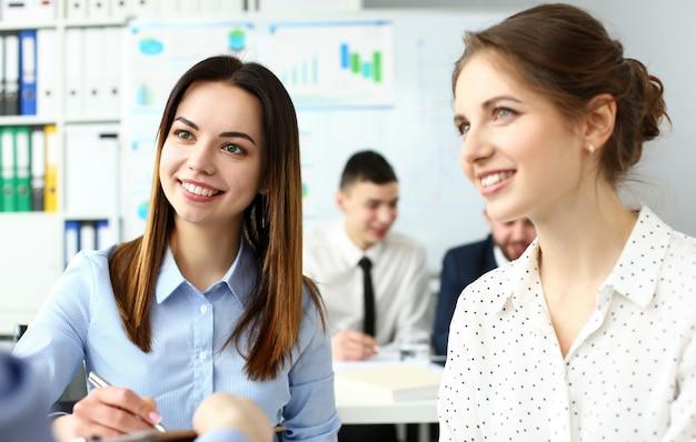 Duas lindas funcionárias brancas, sorrindo, discutindo no escritório um retrato de problemas de negócios