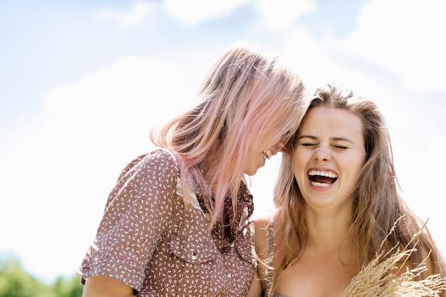 Duas lindas garotas alegres em um fundo de céu claro